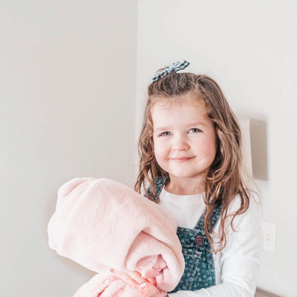 little girl holding her personalized fleece baby blanket